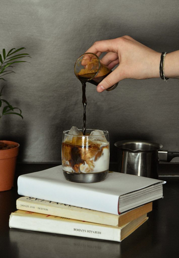 Hand pouring Kahlua into a White Russian cocktail. The cocktail is sitting on a stack of books.